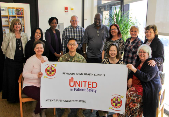 "A dozen members of the Reynolds Army Health Clinic at Fort Sill, Okla. stand behind a ""United for Patient Safety"" banner."