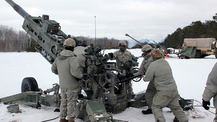 Military personnel standing in the snow preparing to fire a missile
