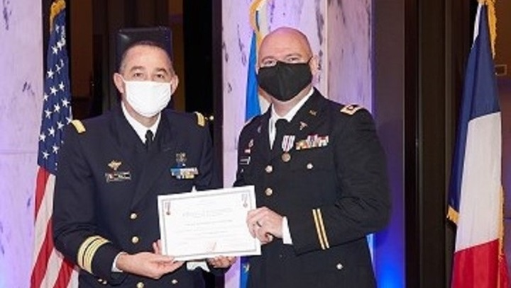 Two military officers on stage; one handing the other a certificate