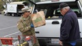 Army Sgt. Moises Castillo of the California Army National Guard helps an Amador County resident load food supplies into a vehicle at the Interfaith Food Bank in Jackson, Calif., March 23, 2020. (U.S. Army photo illustration by Army National Guard Staff Sgt. Eddie Siguenza)