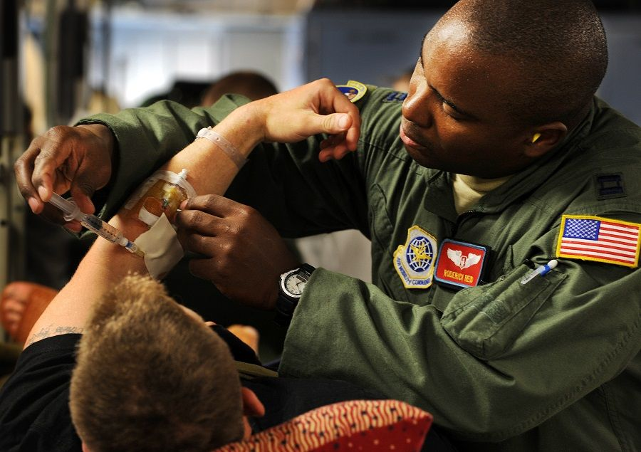 Air Force flight nurse administers pain medication to a patient in transit to home.