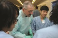 Medical professionals gather in hospital hallway to huddle.