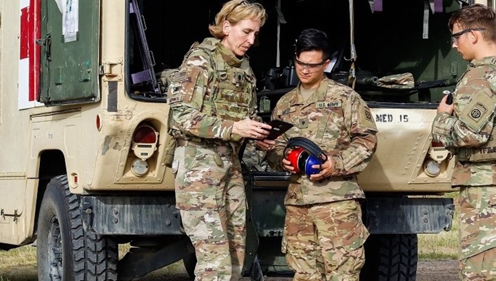Image of three soldiers looking at an iPad