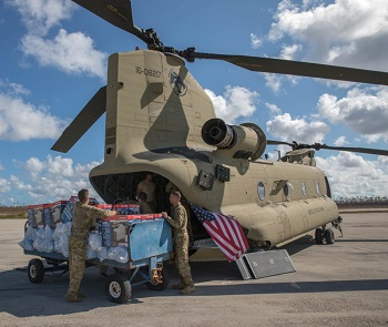 Military personnel unloading equipment from a helicopter