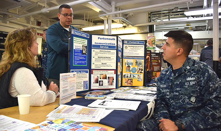 Immunization Healthcare Branch nurse practitioner Ann Morse (left) speaks to Sailors about immunizations at a health fair. The Health Fair was part of a long-range plan to improve the overall health and wellness of Sailors.(U.S. Navy photo by Lt. j.g. Mckensey Smith)
