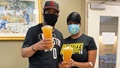 Couple wearing masks, holding bags of plasma