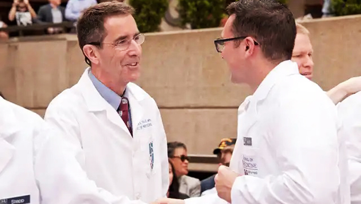 Two men in white medical coats shaking hands