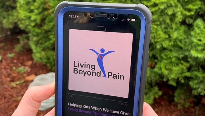 Hands holding a smartphone with the Living Beyond Pain podcast playing on the device.