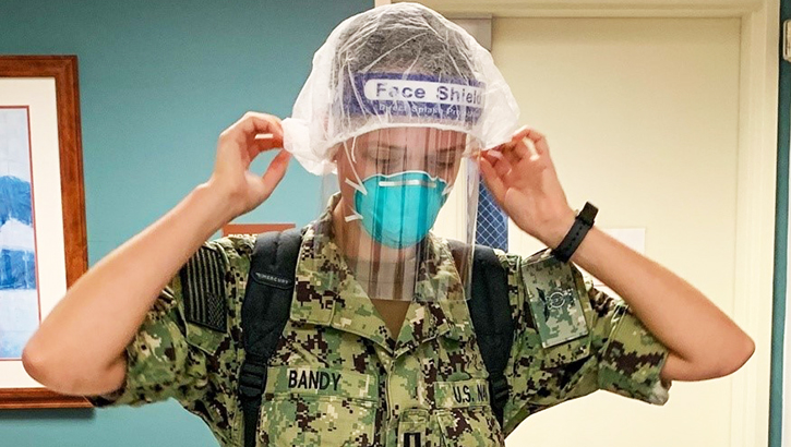 Military nurse putting on PPE
