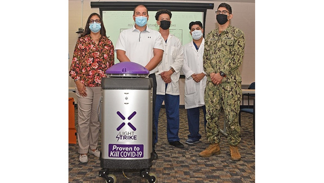 Hospital personnel standing with a cleaning robot