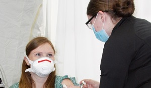 Nurse giving a shot to a girl; both wearing masks