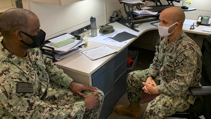 Two military personnel, wearing masks, sitting at a desk talking