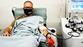 Man wearing mask in hospital chair giving blood