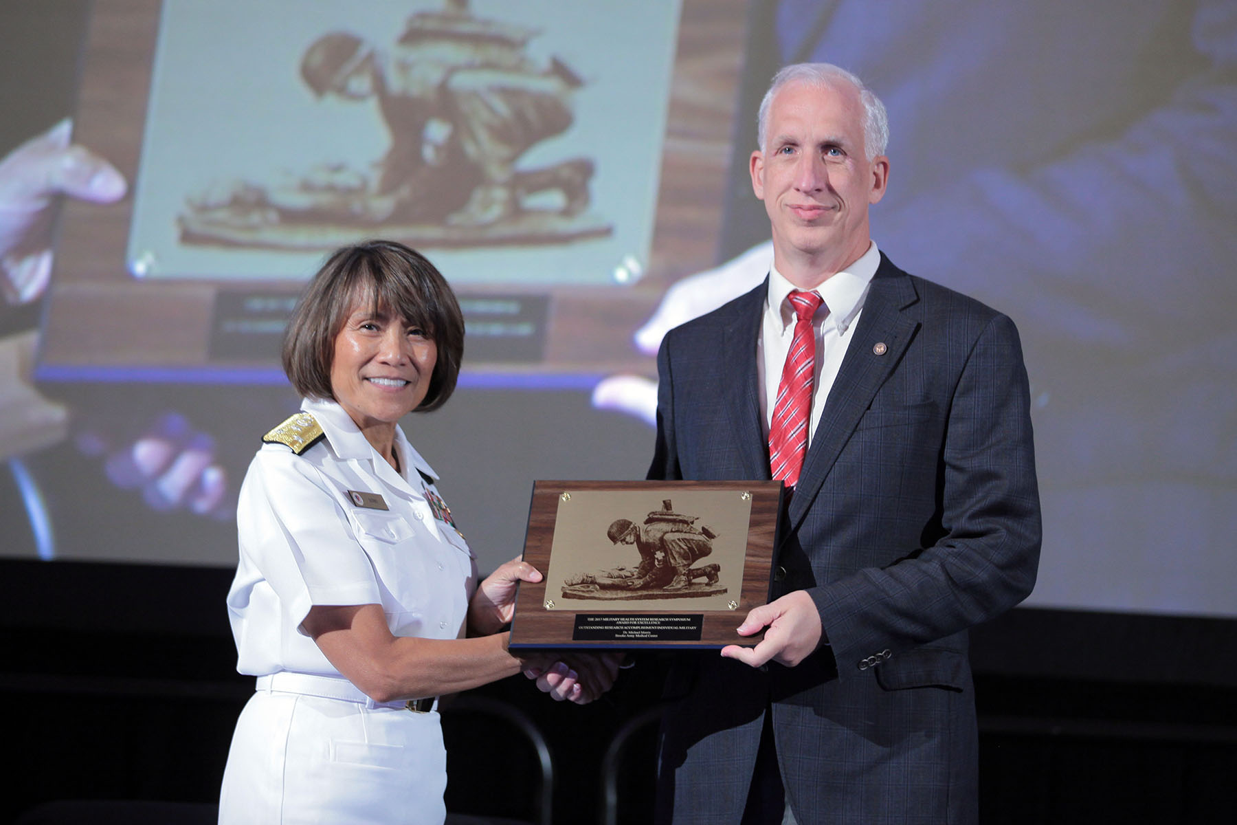 Vice Admiral Raquel C. Bono, director of the Defense Health Agency, presented Michael J. Morris, M.D. with the 2017 Individual Research Accomplishment for civilians, in the category of Occupational Medicine, today at the Military Health System (MHS) Research Symposium. The Individual Research Accomplishment award recognizes outstanding contributions by an individual scientist that had a high impact on MHS research within the past year.  Morris is recognized today for his ongoing research investigating the effects of deployment on respiratory health.