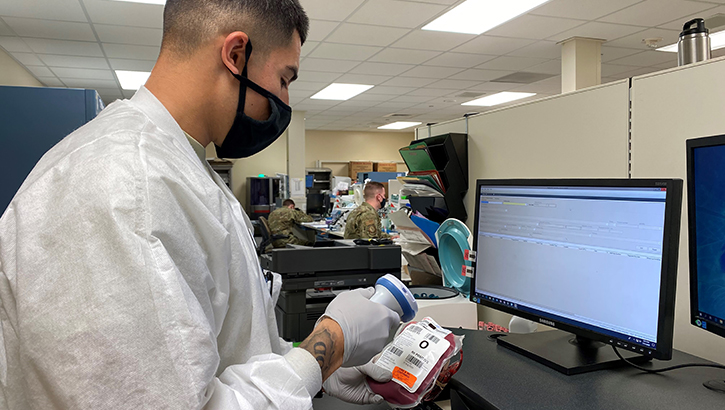 Technician wearing a mask, scanning in a label on a unit of blood.