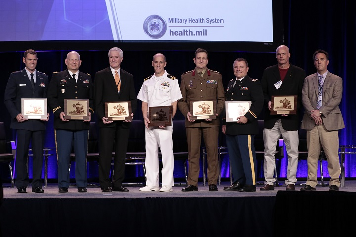 Pictured are the recipients of the 2018 MHSRS Awards, including the 2018 MHSRS Distinguished Service Award, the individual achievement in research awards, and the research team awards. Right to left are Air Force Maj. Joseph K. Maddry, Army Col. Michael P. Kozar, Kenneth M. Hargreaves, DDS, Ph.D., Navy Lt. Cmdr. Micah Gaspary, Australian Defence Force Col. Michael Reade, Army Col. Andrew P. Cap, Dr. Thomas Joiner and Dr. Peter Gutierrez. (MHS photo)