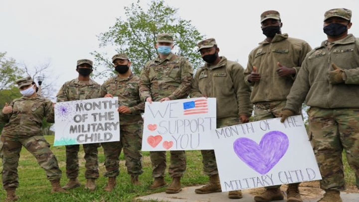 Military personnel wearing face mask holding up posters for Month of the Military Child