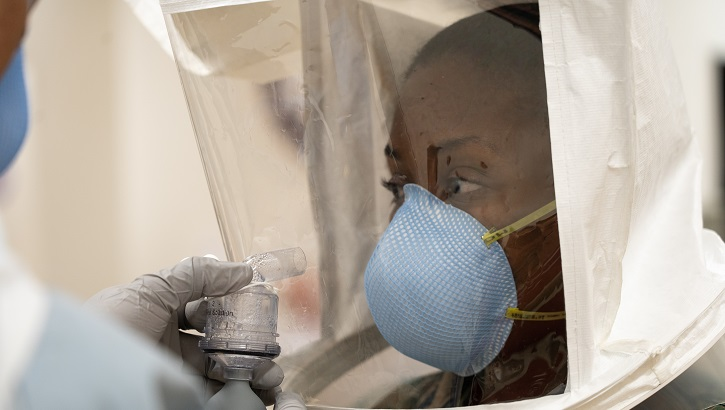 Image of soldier in a hazmat suit with a medical-grade mask