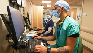 Medical technicians wearing masks and entering information on a computer