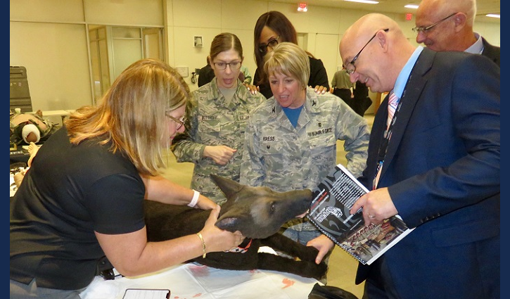 Air Force Col. Christine Kress (center) observes use of a medical canine mannequin designed to create training environments that prepare medical professionals for events they may face in the field. (MHS photo)