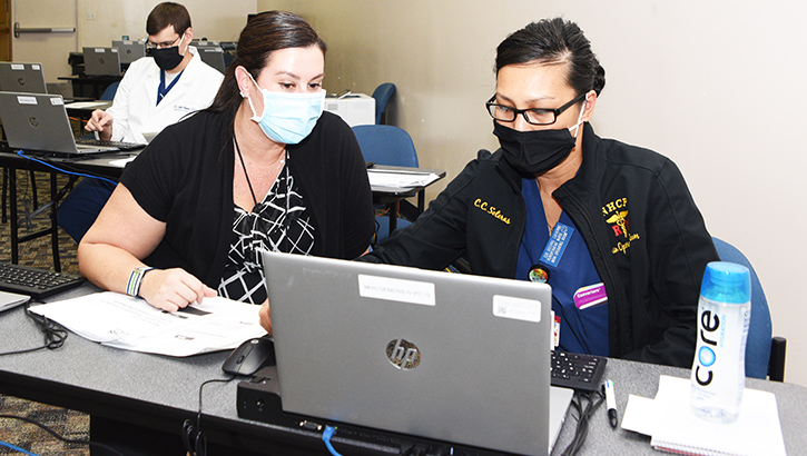 Two women in masks, sitting at laptop