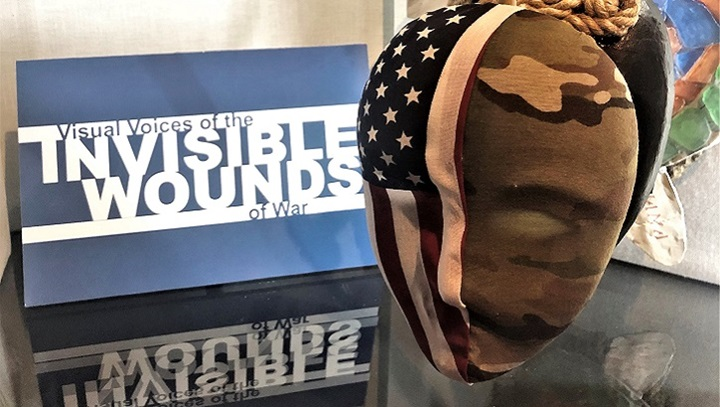 Picture of a mask with the American flag on one side and camo on the other side