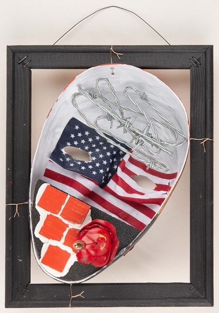 "This papier-mâché mask decorated with barbed wire, ceramic tiles, bullet casings, and an American flag is titled ""Breaking Through the Pain."" It was made by a patient in the Creative Arts Therapy Program at the National Intrepid Center of Excellence at Walter Reed National Military Medical Center. It is displayed as part of the National Museum of Health and Medicine's ""Visual Voices of the Invisible Wounds of War"" exhibit which runs through May 31. (Disclosure: This image has been cropped to emphasize the subject.) (Department of Defense photo by Matthew Breitbart)"