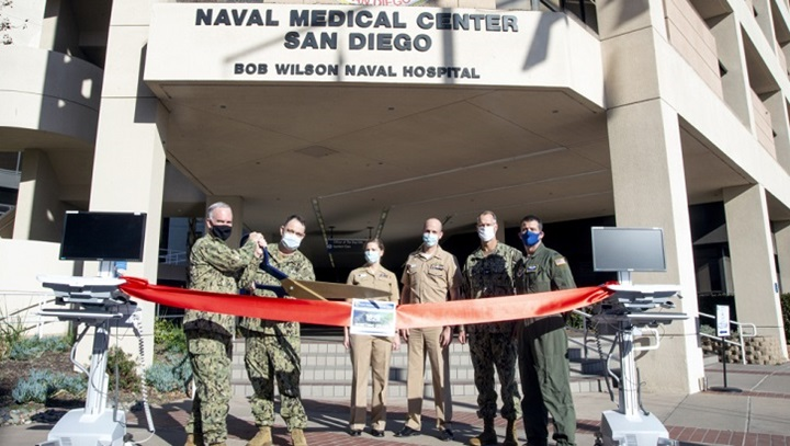 Military personnel standing in front of Naval Medical Center cutting a red ribbon