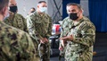 Military health personnel wearing face mask discussing the COVID-19 vaccine program