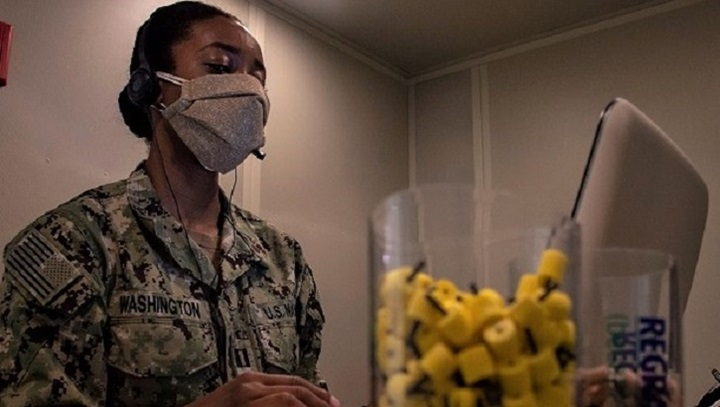 Soldier wearing mask, sitting at laptop with a container of ear plugs close by