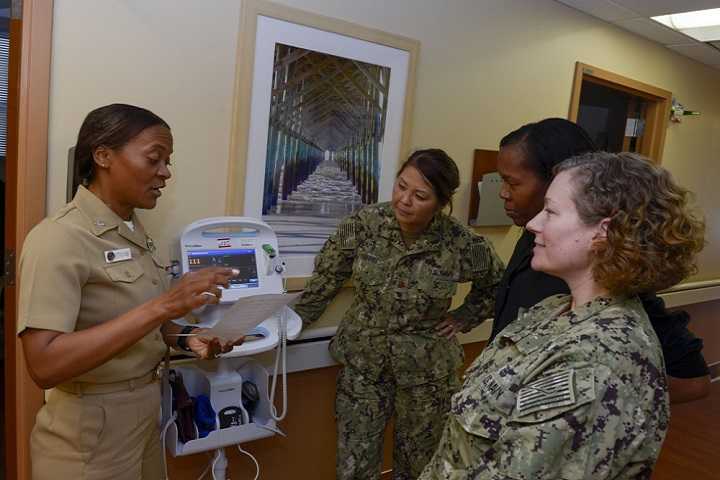Navy Capt. Andrea Petrovanie (left), Naval Medical Center San Diego, Senior Nurse Officer, Directorate for Branch Clinics, goes over the day's orders with members of her nursing staff at NMCSD Naval Training Center branch clinic. Petrovanie was recently recognized for outstanding leadership by the American Nurses Credentialing Center and the Defense Health Agency. (U.S. Navy photo)