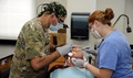 Army Maj. Jesus Morales, dentist, 49th Multifunctional Medical Battalion, Puerto Rico, and U.S. Air Force Senior Airman Jessica Hawk, dental assistant, 172d Airlift Wing, Jackson Mississippi, extract a decayed tooth from Raymond Kline. Kline participated in the no-cost medical services offered during the Ozark Highlands Innovated Readiness Training, Mountain Home, Arkansas, recently. (U.S. Air Force photo by Tech. Sgt. Peter Dean)