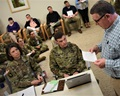 Civilian and military staff at Irwin Army Community Hospital are gathered in a room to briefly discuss quality and safety concerns across the organization. Mr. Jon Cranmer, head of facilities stands to give his update.