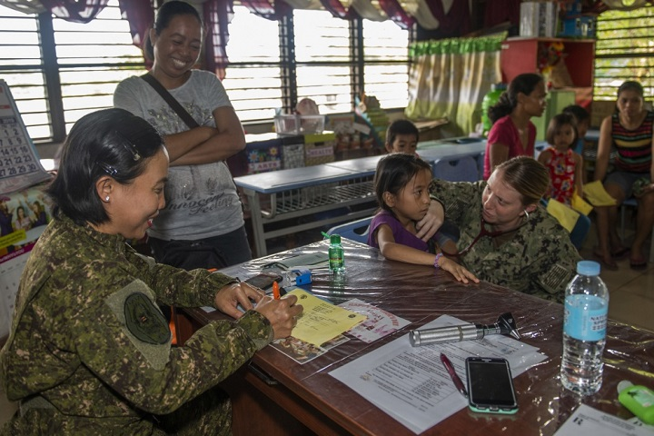 Navy Lt. Sharon Hoff (right) listens to a patient's heartbeat as Philippine Army Capt. Glorife Saura from the Armed Forces of the Philippines Medical Corps records patient vital signs. Pacific Partnership participants and Tacloban City medical professionals worked together to provide medical and veterinary services throughout the day at Tigbao Diit Elementary School. (U.S. Navy photo by Mass Communication Specialist 1st Class Nathan Carpenter)