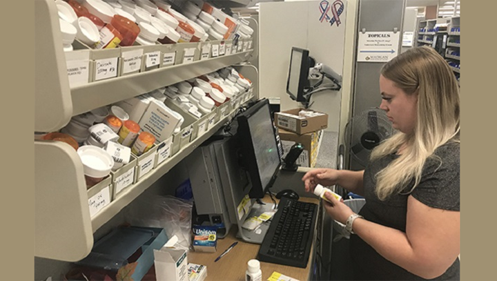 Pharmacist Ashley Burrill fills a prescription at the Madigan pharmacy on July 23. Assigning staff to their strongest roles helped to reduce the pharmacy wait time. (U.S. Army photo by Suzanne Ovel)