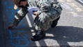 Military personnel wearing a face mask writing messages with chalk on the ground