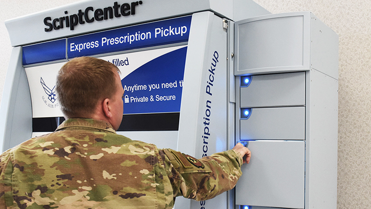 A pharmacy technician opens a locker holding prescription medication