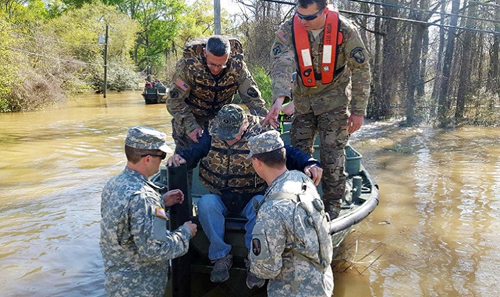 Louisiana National Guard Soldiers with the 2225th Multi-Role Bridge Company, 205th Engineer Battalion, help a man out of the bridge erection boat they used to check on residents affected by flooding in Ponchatoula, Louisiana. (U.S. Army photo by 1st Lt. Rebekah Malone)