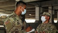 Two military personnel with mask on talking, while one is writing on a notepad