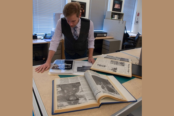 Trenton Streck-Havill, assistant archivist in the National Museum of Health and Medicine's Otis Historical Archives (OHA), finishes identifying Service Stripe newspaper source photos by searching through film negatives from the Walter Reed Army Medical Center Archives that are included in the OHA's collections.  In May 2018, the OHA acquired 64 bound volumes of Service Stripe and 87 bound volumes of Stripe from Walter Reed National Military Medical Center.  The weekly newspaper ceased publication in 2011. (National Museum of Health and Medicine photo by Matthew Breitbart)