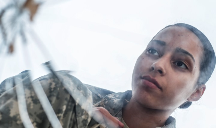 Army Private 1st Class Luselys Lugardo, a soldier assigned to the New Jersey Army National Guard, poses in front of a shattered mirror for a portrait. The shattered glass represents the way suicide hurts families, friends and coworkers. (U.S. Air Force photo by Tech. Sgt. Matt Hecht)