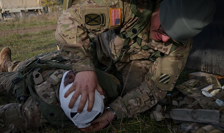 U.S. Army Sgt. Eric Puglio, right, of Foxtrot Battery, 1st Battalion, 41st Field Artillery Regiment, 1st Armored Brigade bandages Army Sgt. Derrick Rouse's head after he received a simulated injury. (U.S. Army photo by Staff Sgt. Carol A. Lehman)