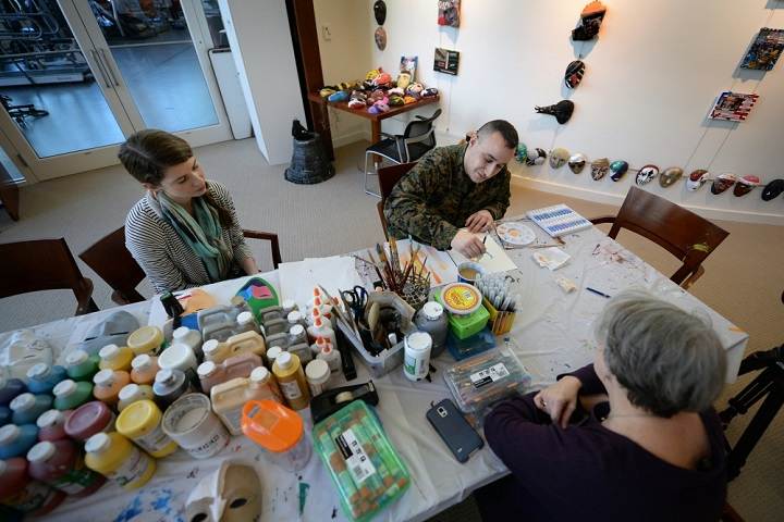 Marine Corps Staff Sgt. Anthony Mannino performs Art Therapy as part of his Traumatic Brain Injury (TBI) treatment and recovery. Art Therapy Interns, Adrienne Stamper (left) and Nancy Parfitt instruct and work with Mannino as he receives his art therapy. The therapy is conducted at the National Intrepid Center of Excellence, Walter Reed National Military Medical Center located in Bethesda, Maryland. (Department of Defense photo by Marvin Lynchard)