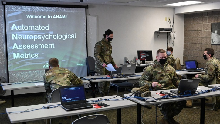 A group of military personnel wearing face mask working on laptop computers