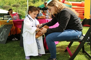 A corpsman teaches a child how stethoscopes work. During the Teddy Bear Health Clinic, children received a teddy bear, went from station to station making sure their new friend was healthy. The bears received patient identification bracelets, had their blood pressure taken, their hearts listened to, hearing tested, and even experienced an x-ray. The goal was to introduce children to different departments in the hospital and help alleviate any anxiety during future appointments or potential hospital stays. (U.S. Navy photo by Christina Clarke)