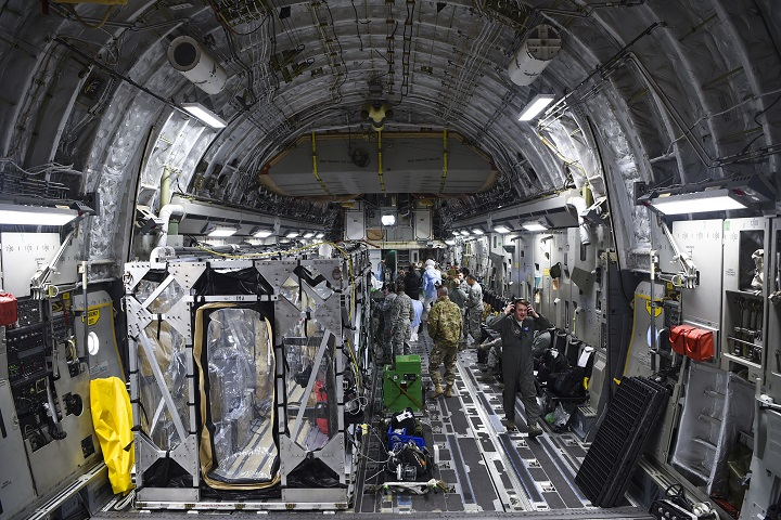 A C-17 Globemaster III is prepped to transport a Transportation Isolation System during a training exercise that allows Airmen to practice the most effective and safest form of transportation for patients and their medical professionals. Engineered and implemented after the Ebola virus outbreak in 2014, the TIS is an enclosure the Defense Department can use to safely transport patients with highly contagious diseases. (U.S. Air Force photo by Senior Airman Cody Miller)