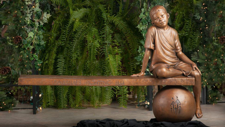 A bronze bench and statue near the America Building at Walter Reed National Military Medical Center in Bethesda, Maryland, memorializes military dependent Trevor Lin. The 7-year-old's death in the fall of 2009 was attributed to influenza.  (Photo courtesy of Walter Reed-Bethesda)