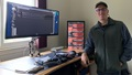 Image of man standing next to large computer screen