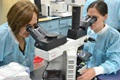 Navy LCDR Kimberly Edgel (right) and Carmen Lucas examine a positive malaria blood smear at U.S. Naval Medical Research Unit, or NAMRU, 6 in Callao, Peru. (U.S. Navy photo)