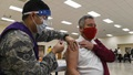 Military health personnel wearing a mask giving the COVID-19 vaccine to a man who is also wearing a face mask